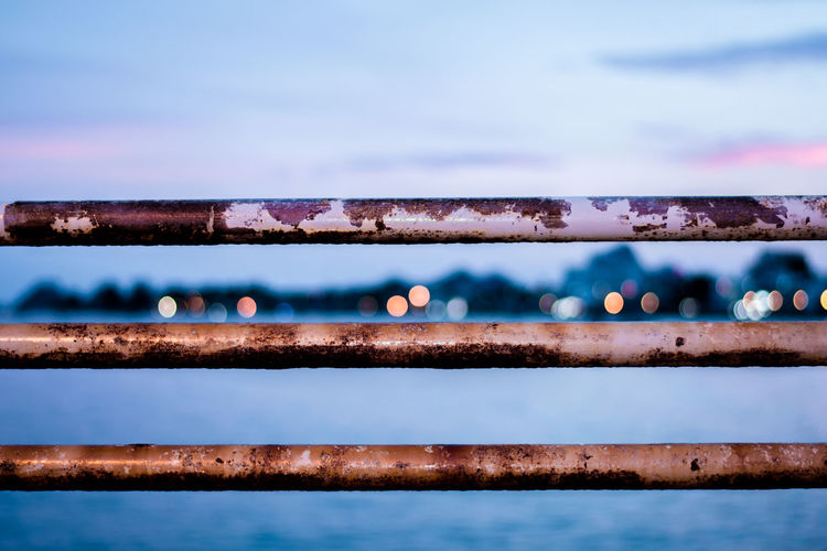 Railing and sea against sky during sunset
