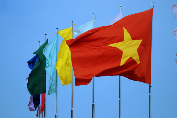 Close-Up Of Flags Against Clear Blue Sky