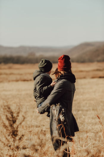Child in knitted warm green hat inhis mother arms in maroon hat , warmly hugging  inautumn landscape