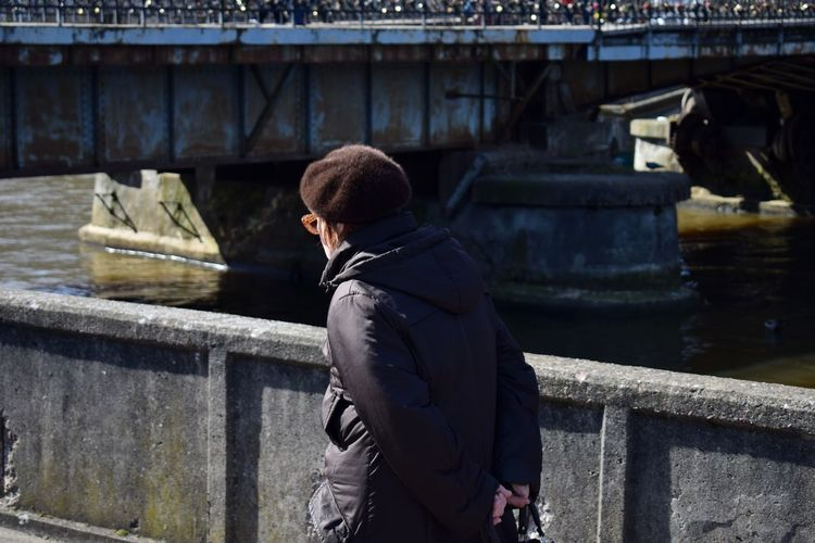 Rear view of man with hands behind back walking on bridge