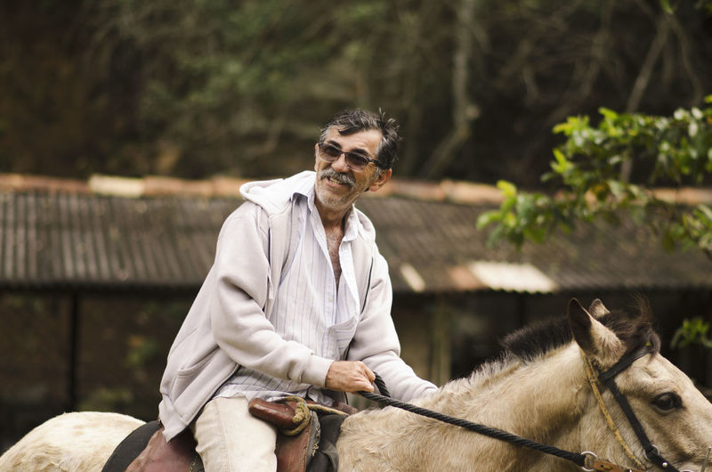 Smiling man in sunglasses riding horse against tree