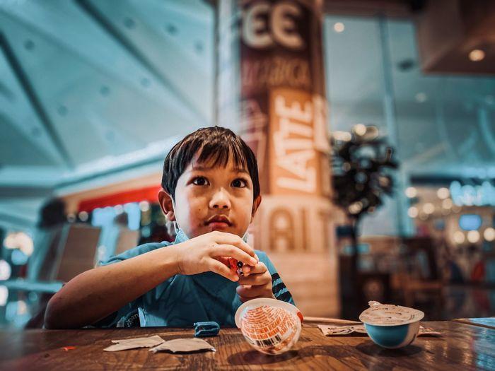 Portrait of boy eating food at restaurant
