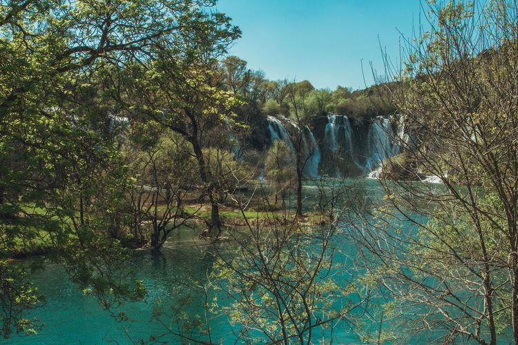 Tourist Attraction  Beauty In Nature Day Flowing Water Forest Growth Kravice Waterfalls Kravmaga Lake Land Nature No People Non-urban Scene Outdoors Plant Reflection Scenics - Nature Sky Tranquil Scene Tranquility Travel Destinations Tree Water Waterfall Waterfront