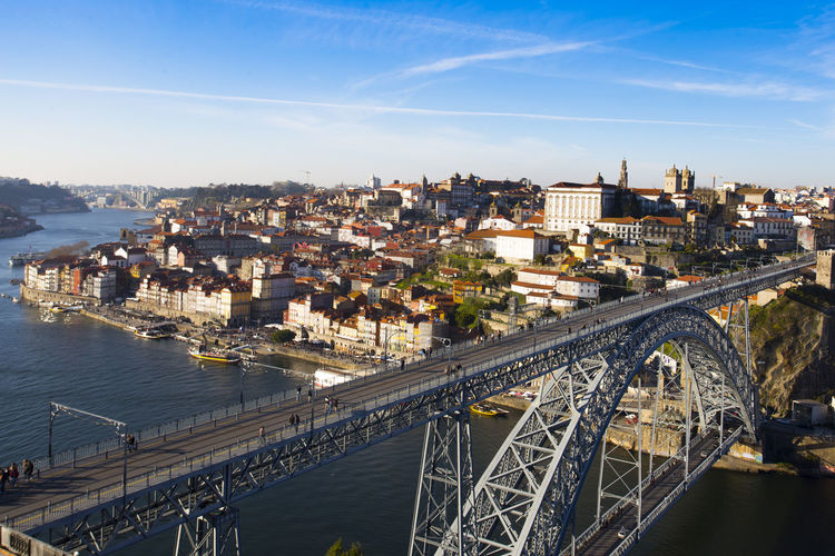 Don luís bridge at porto- portugal. high angle view of river amidst buildings in city against sky