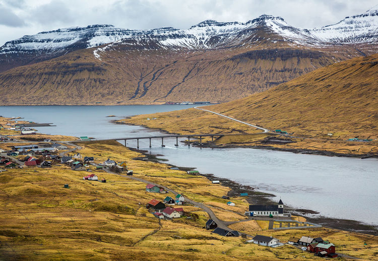 Mountain Scenics - Nature Beauty In Nature Snow Cold Temperature Water Tranquil Scene Nature Mountain Range Winter Non-urban Scene Tranquility Day Environment Snowcapped Mountain Landscape Idyllic Outdoors River Bridge Faroe Islands High Angle View Houses