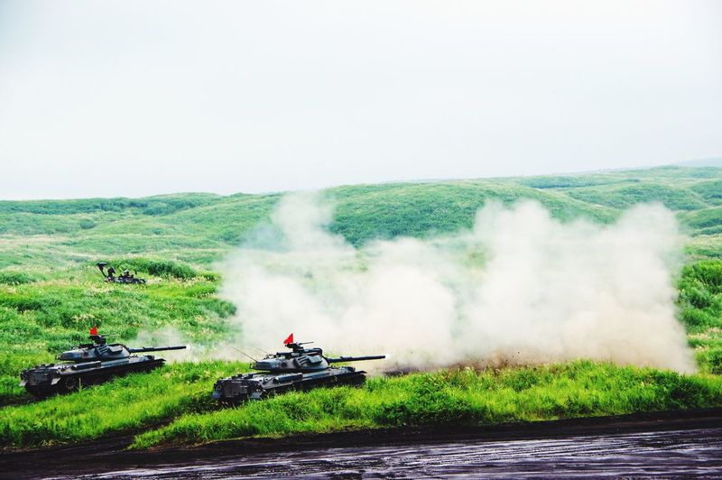 Armored Tanks Firing On Grassy Field Against Sky