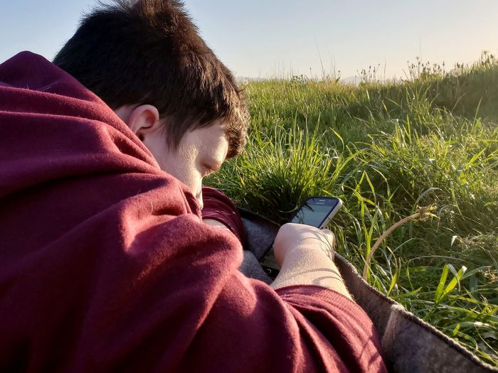 Quality time with my son Sunset Relaxing Summer Days New Perspective Grass And Sun Lazy Days Bug's Eye View Beauty In Nature Sequim EyeEm Selects Wireless Technology Child Sitting Relaxation Grass Close-up Sky Hooded Shirt Hiker Personal Perspective Low Section Blanket Hood - Clothing Summer Exploratorium