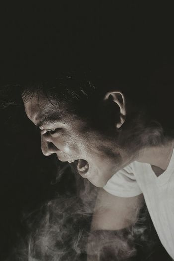 Side View Of Angry Young Man Emitting Smoke Against Black Background