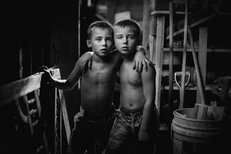 Portrait of shirtless brothers standing at home