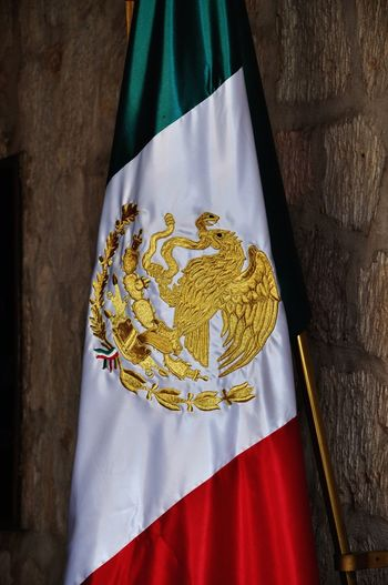 Close-up of mexican flag hanging on wall