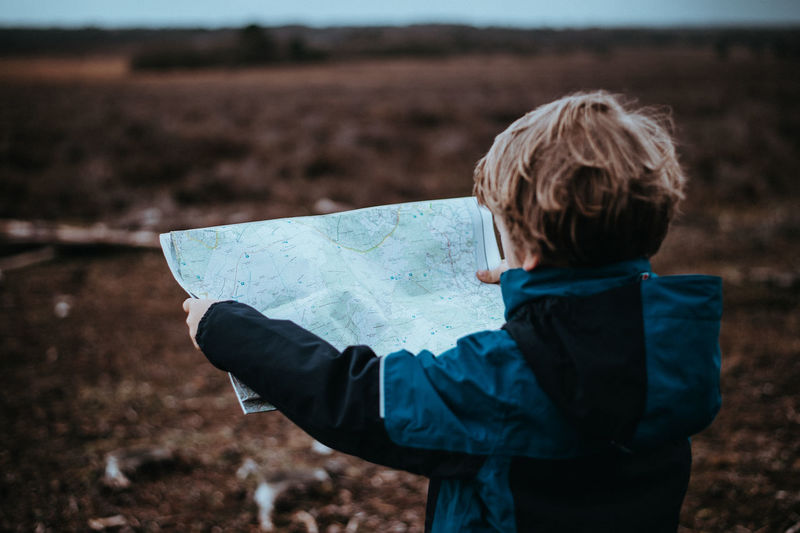 Child holding a map, exploring and navigating the outdoors Exploring Map Boys Child Childhood Exploration Holding Kid Navigating Navigation Ourdoors Outdoors Rear View
