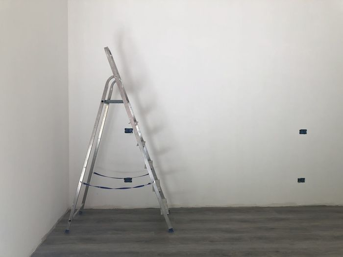 Low angle view of empty ladder against wall