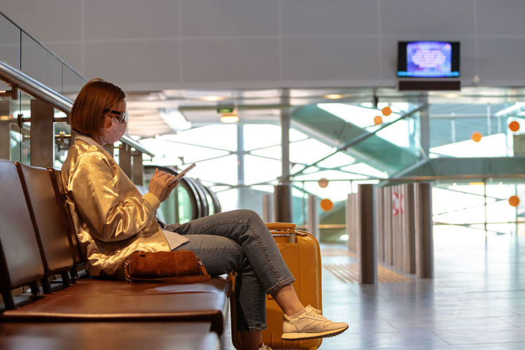 Side view of woman wearing mask using phone while sitting on chair at airport