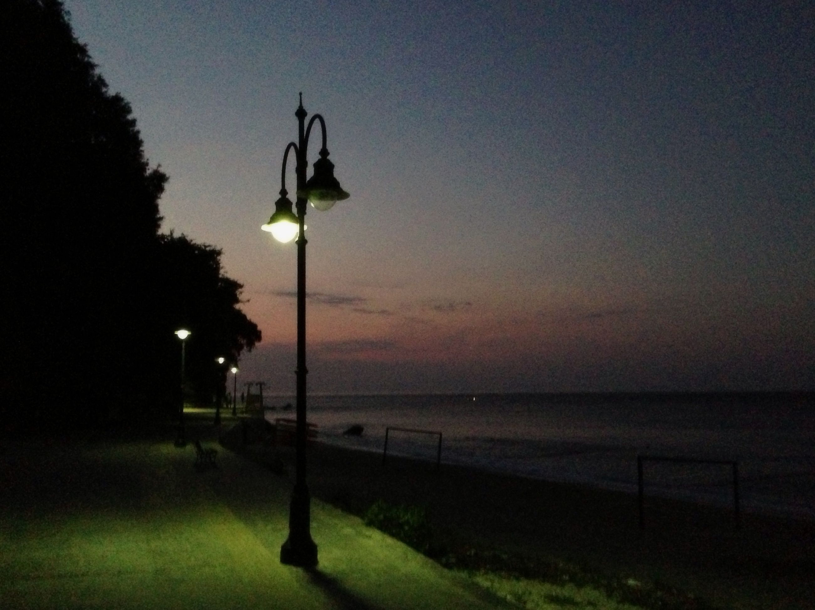 street light, water, sea, sky, tranquility, lighting equipment, silhouette, sunset, tranquil scene, nature, scenics, beauty in nature, horizon over water, dusk, lamp post, idyllic, pole, outdoors, no people, tree