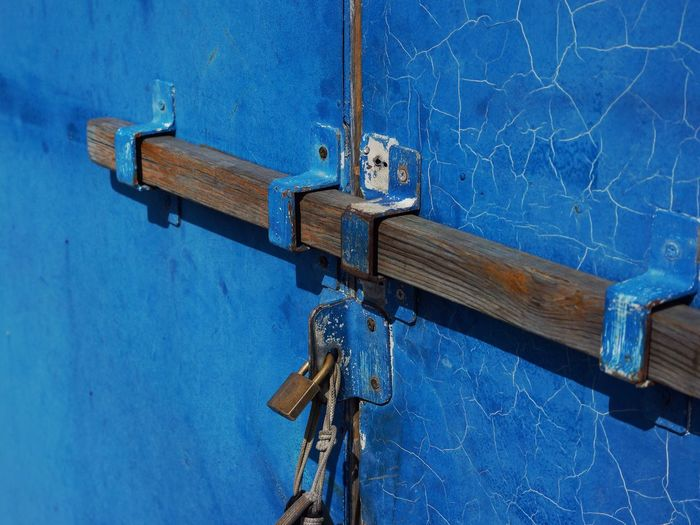 Close-up of padlocks on blue metallic structure