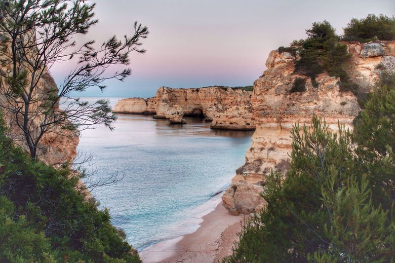 Rock Formations In Sea At Praia Da Marinha During Sunset