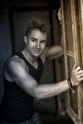 Handsome man looking away while standing by door
