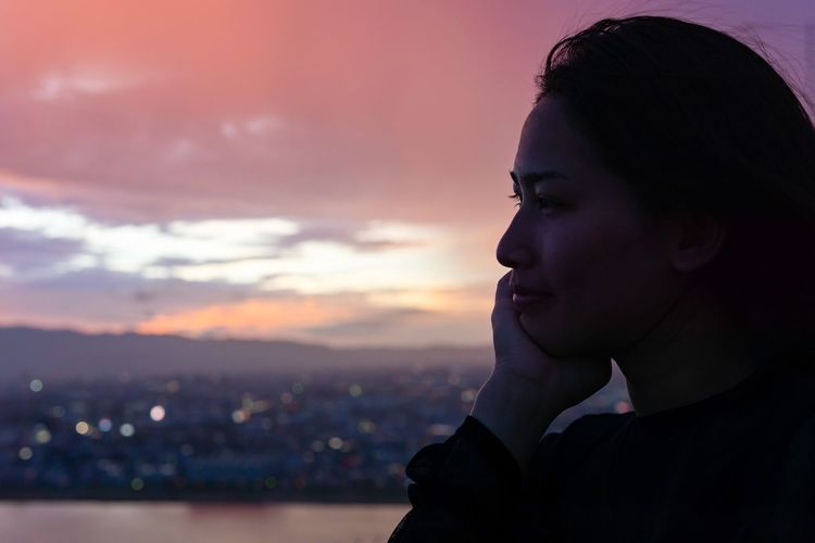 Close-Up Of Thoughtful Young Woman Looking Away Against Sky At Sunset