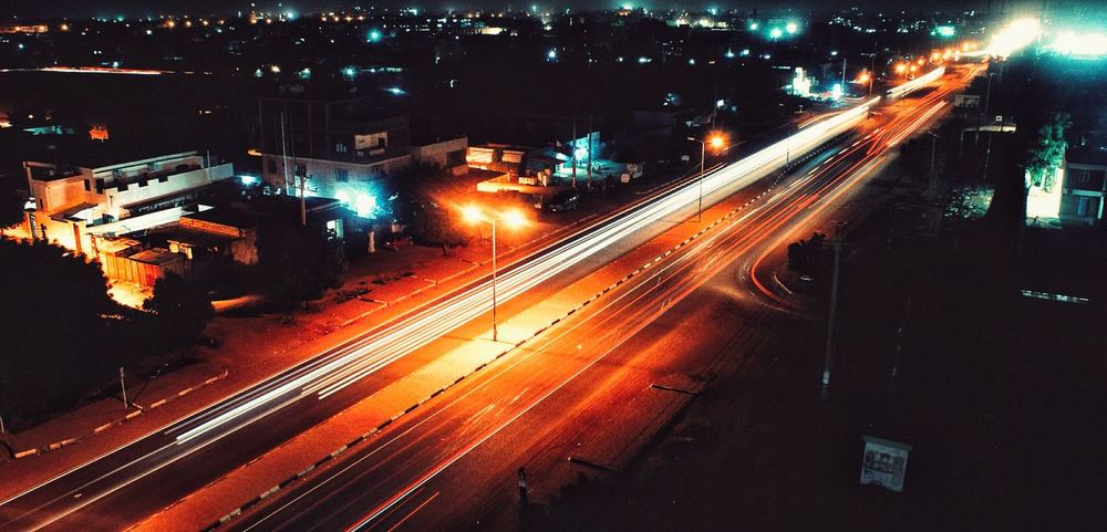 Night Illuminated City Motion Light Trail Long Exposure Street Light Transportation Traffic Speed High Angle View City Life No People Building Exterior Road Built Structure Architecture Outdoors Slow Shutter