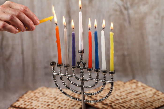 Menorah with candles for Hanukkah on a light wooden in the background. Birthday Birthday Cake Birthday Candles Burning Candle Chanukah Close-up Event Finger Fire Fire - Natural Phenomenon Flame Hand Hanukkah Heat - Temperature Human Body Part Human Hand Illuminated Indoors  Matzo Matzoth Menorah Nature One Person Table
