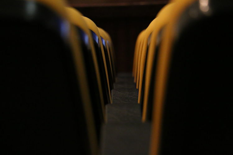 Cinema In Your Life Cinema Show Stage Row Chairs Chair Black Yellow Organized Abstract Close-up Column Corridor Dark Diminishing Perspective Empty Focus On Foreground Illuminated In A Row No People Selective Focus Surface Level The Way Forward Vanishing Point