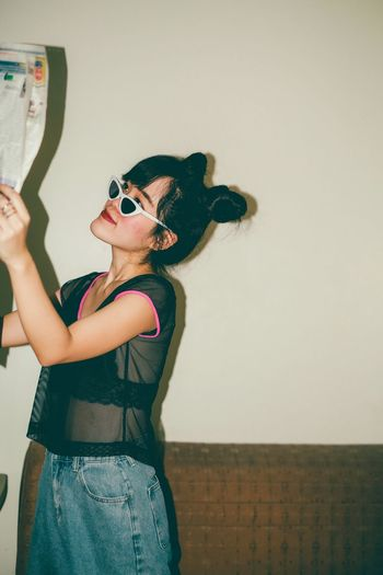 Woman wearing sunglasses standing against wall