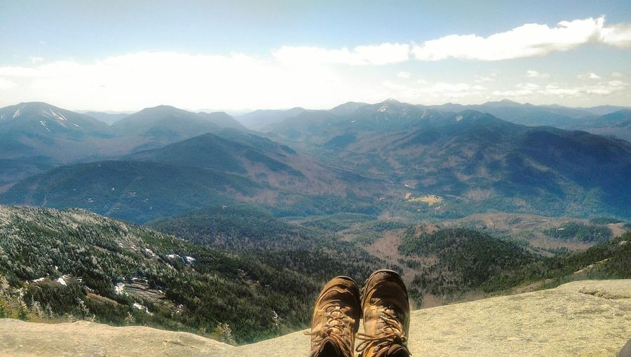 Low section of man at adirondack mountains against sky