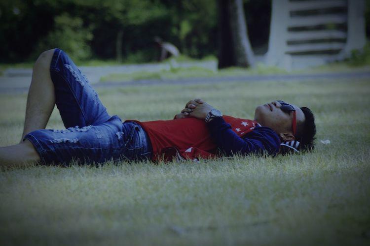 Rear view of boy lying on grass in field