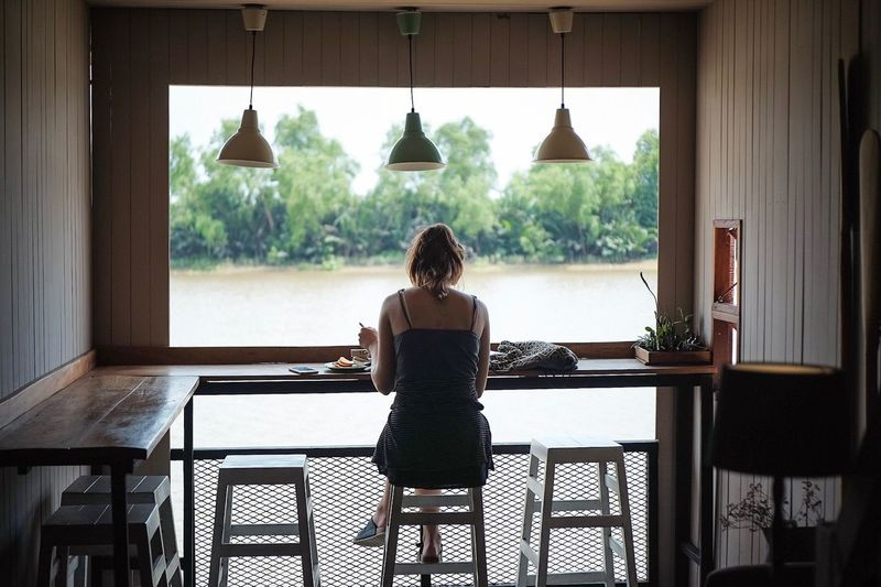Rear View Of Woman Sitting At Table In Restaurant Against Lake