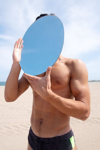 Shirtless man holding mirror while standing at beach against sky