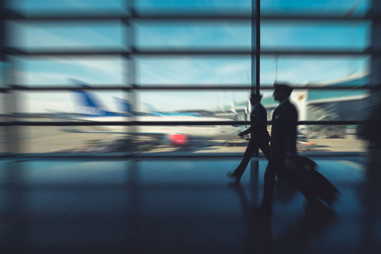 Blurred image of two pilots walking in an airport with airplanes in the backgroundTravel Traveling Blurred Motion Men Motion People Pilot Pilots Walking Airport Airplane Aviation Work Job Captain Air Vehicle Airplanes Pilot's Life