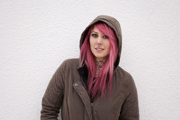 Portrait Of Young Woman In Pink Hair Standing Against Wall