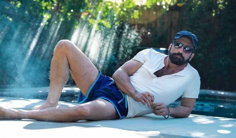 Man wearing sunglasses reclining at poolside