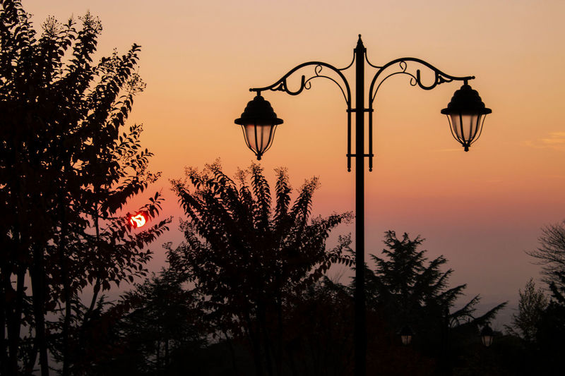 Low angle view of silhouette street light against sky at sunset