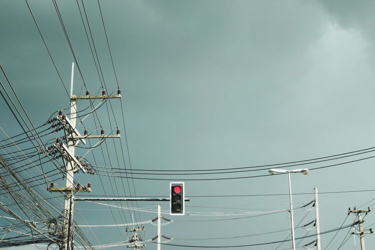 Low Angle View Of Tangled Cables By Traffic Signal Against Sky