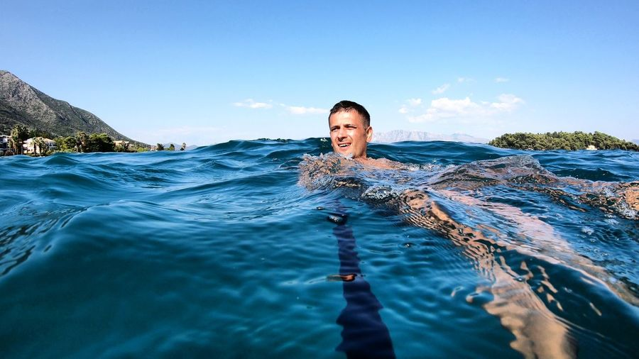 Portrait of smiling man swimming in sea against sky