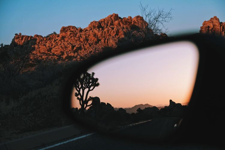 Clear sky reflecting on side-view mirror at sunset