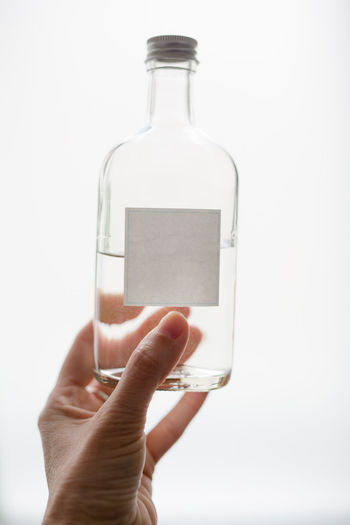 Label Opaque Water Liquid Alcohol Medicine Human Hand Holding Bottle Container Human Body Part Hand One Person Indoors  Studio Shot Finger White Background Glass - Material Human Finger Close-up Transparent Unrecognizable Person Body Part Adult Real People Blank Copy Space No Text