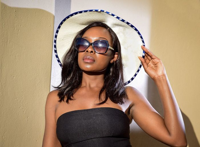 Woman wearing sunglasses and hat against wall
