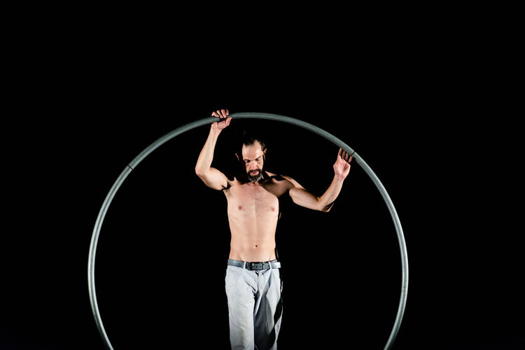 Circus Adult Arms Raised Black Background Front View Human Arm Human Body Part Human Limb Indoors  Limb Males  Men Muscular Build One Person Performance Plastic Hoop Shirtless Skill  Standing Studio Shot Three Quarter Length Young Adult