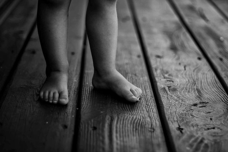 Feet Wood - Material Barefoot Low Section Human Leg Real People Childhood One Person Human Foot Human Body Part Leisure Activity Hardwood Floor Lifestyles Child Standing Indoors  Day Close-up Children Only People