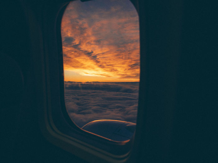 Fire in the Sky Air Vehicle Airplane Beauty In Nature Cloud - Sky Flying From An Airplane Window Glass - Material Mode Of Transportation Nature No People Orange Color Scenics - Nature Sky Sunset Transparent Transportation Travel Vehicle Interior Window
