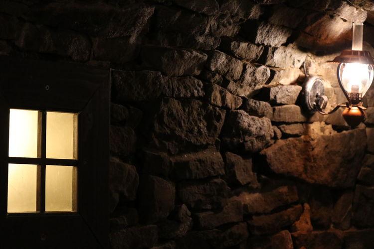 Stone wall with illuminated lamp