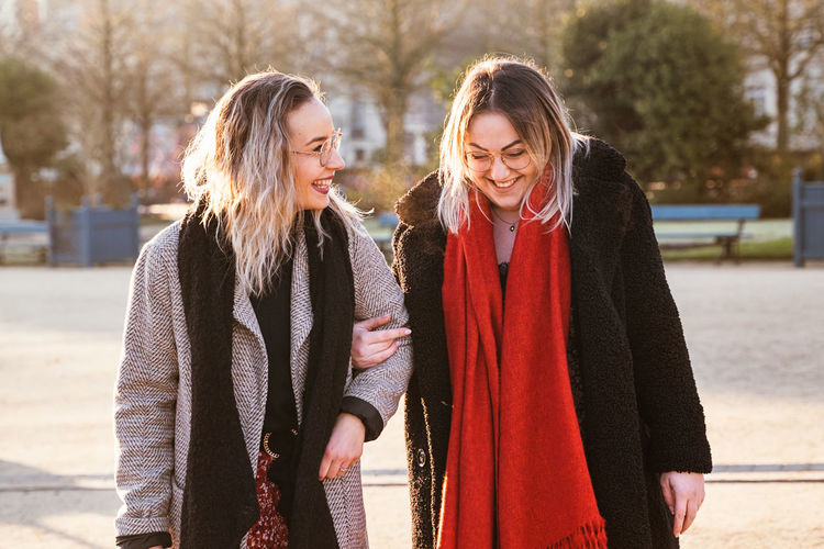 Smiling female friends talking while walking in park