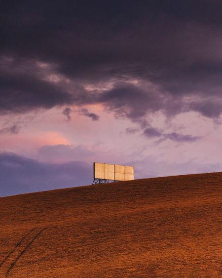 Billboard on land against sky during sunset