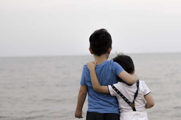Rear view of boys standing at sea against sky