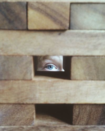 Person Looking Through Block Hole