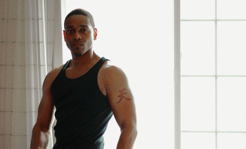 Portrait of muscular man standing window