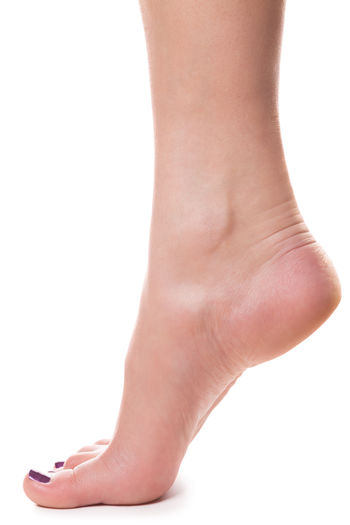 Low section of woman tiptoeing on white background