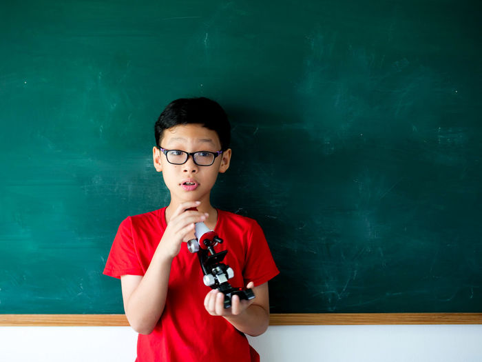 Portrait Of Boy Wearing Eyeglasses While Holding Against Black Board